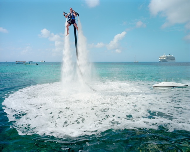 An employ of 'Jetpack Cayman' demonstrates the watersport now available on the island. A 2000cc motor pumps up water trough the Jetpack propelling the client out of the water (359US$ for a 30 minutes secession). Mike Thalasinos, the owner of the company quips, 'the Jetpack is zero gravity, the Cayman are zero taxes, we are in the right place!' Grand Cayman. Courtesy of the artist.